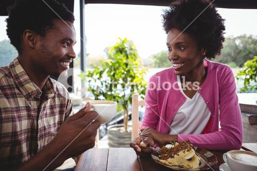 Young couple having breakfast in cafeteria