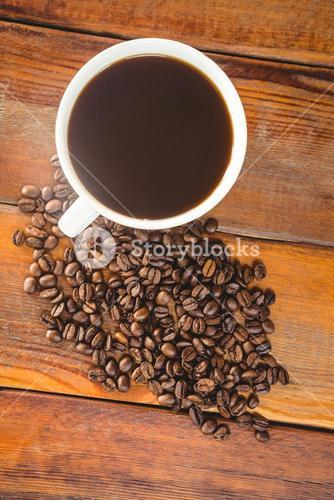 Cup of coffee with coffee beans on table