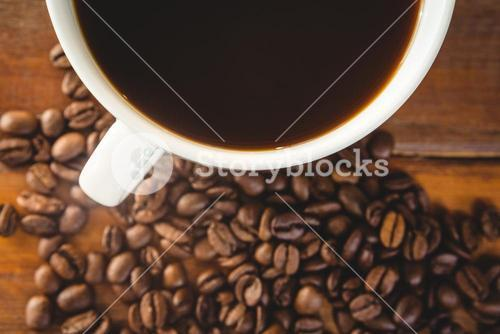 Close-up of coffee cup with coffee beans on table