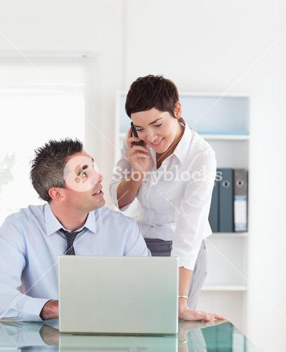Portrait of a woman making a phone call while her colleague is working on a laptop