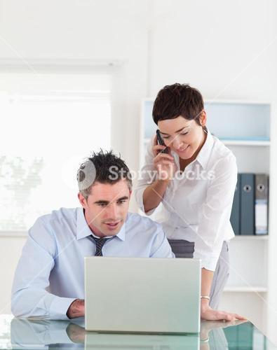 Portrait of a woman making a phone call while her colleague is looking at a laptop