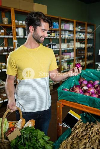 Man buying onion in supermarket