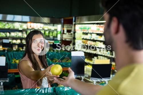 Woman giving fruit to cashier for billing at supermarket