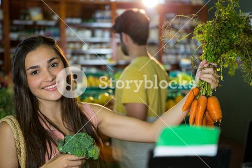 Woman buying bunch of carrots and broccoli in supermarket