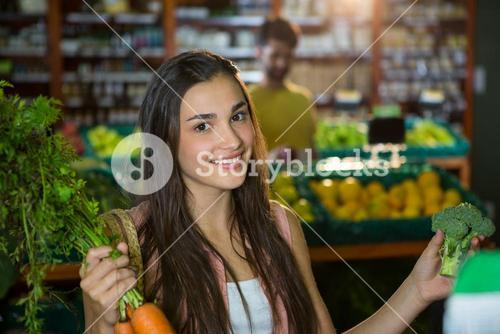 Woman buying carrot and broccoli in supermarket