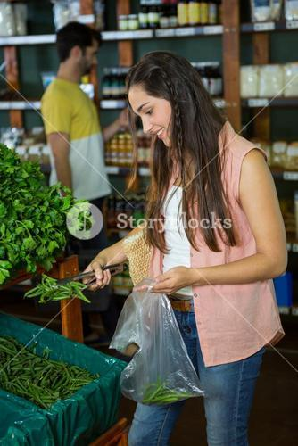 Woman shopping for fresh vegetables in organic section