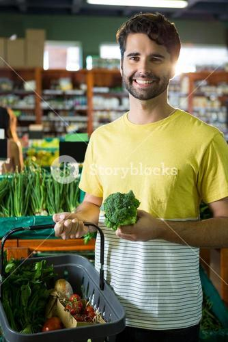 Portrait of handsome man buying broccoli and different vegetables in organic section