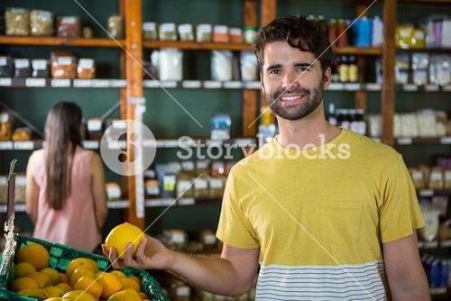 Portrait of handsome man buying sweet lime in organic section