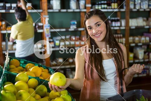 Portrait of beautiful woman buying sweet lime in organic section