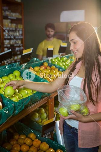 Woman selecting green apples in organic section