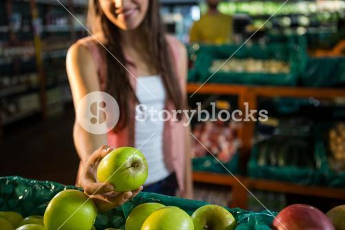 Woman selecting a green apple in organic section
