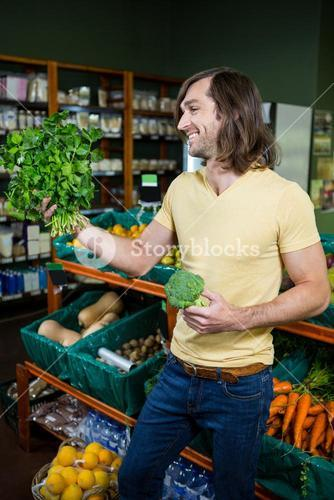 Man holding bunch of herbs and broccoli in organic section