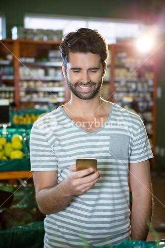 Smiling man using his phone in the organic section