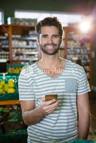 Portrait of smiling man using his phone in the organic section