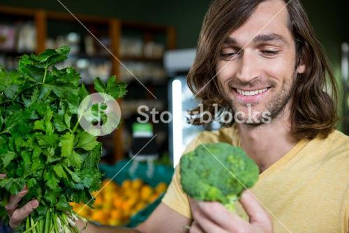Happy man holding broccoli and bunch of herbs and in organic section