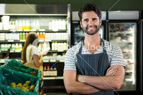 Portrait of smiling male staff standing with arms crossed in organic section
