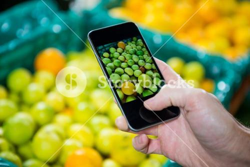 Hand photographing a fruits