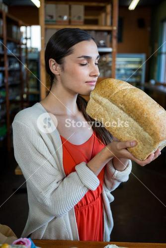 Woman smelling a loaf of bread