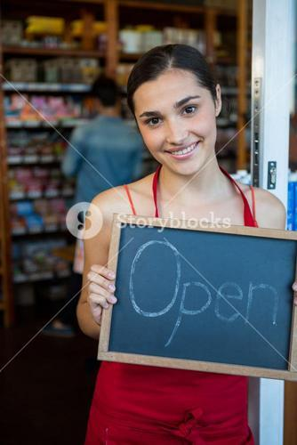 Woman holding open signboard