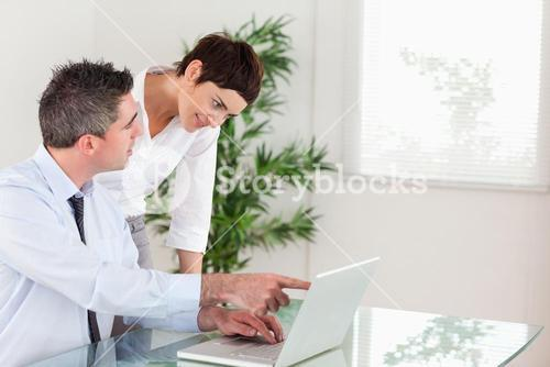 Man pointing at something to his colleague on a laptop