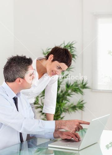 Portrait of a man pointing at something to his colleague on a laptop