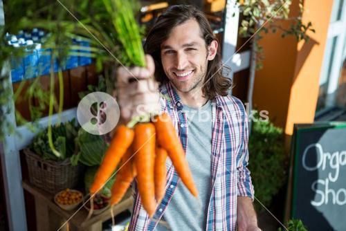 Man holding carrots in organic shop
