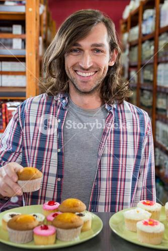 Happy man with a plate of cupcakes