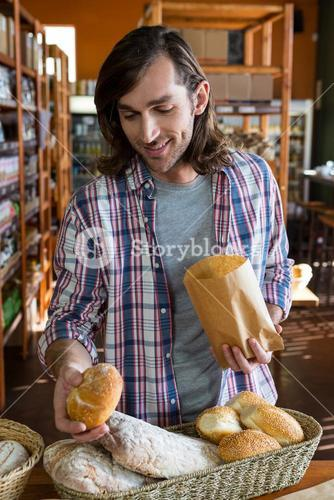 Man buying loaf of bread