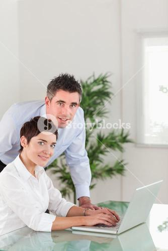 Portrait of a manager and his secretary posing with a laptop