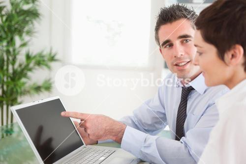 Manager pointing at something to his secretary on a laptop