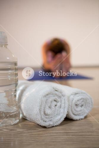 Rolled towels and water bottle in fitness studio