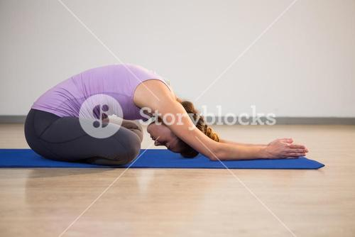 Woman doing yoga child pose on exercise mat