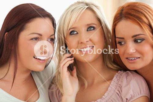 Cute women sitting on a sofa with a mobile