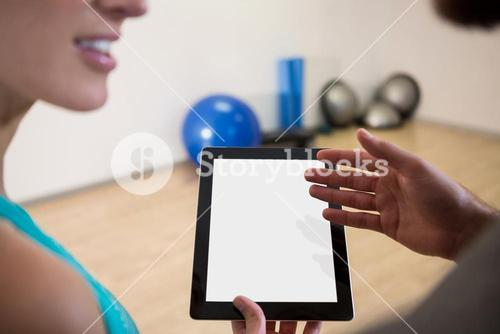 Fitness trainer showing digital tablet to woman