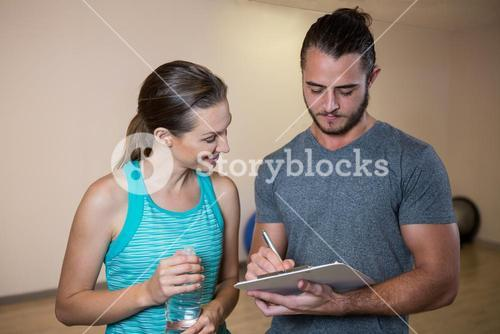 Fitness trainer and woman looking at clipboard