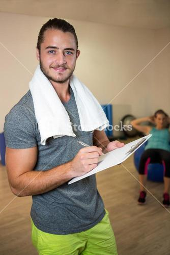 Portrait of smiling fitness trainer writing on clipboard
