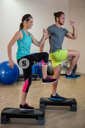 Man and woman doing step aerobic exercise on stepper