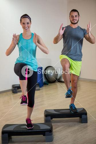 Smiling man and woman doing step aerobic exercise on stepper