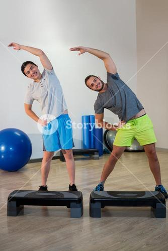Portrait of two men doing aerobic exercise with stepper