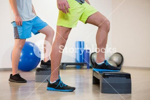 Two men doing step aerobic exercise on stepper