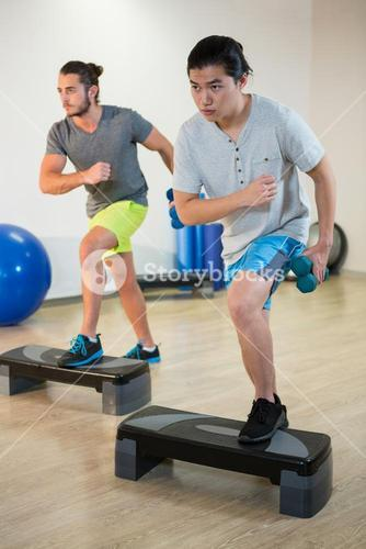 Two men doing step aerobic exercise with dumbbell on stepper