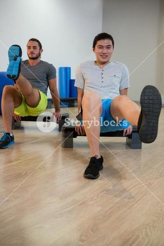 Two men doing aerobic exercise on stepper