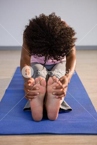 Woman doing seated forward on bend exercise mat