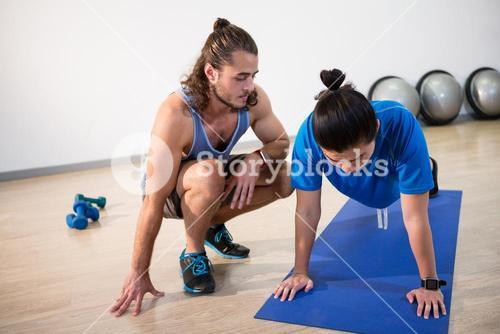Fitness instructor helping fitness man with push-up