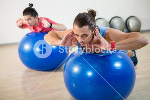 Men exercising on exercise ball
