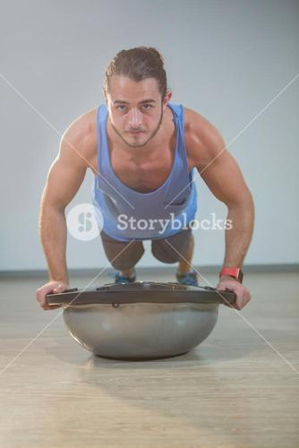 Man doing push-up on bosuball