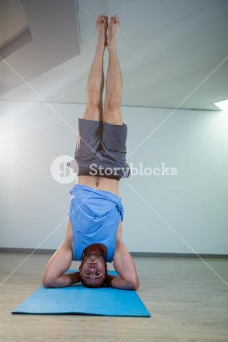 Man performing sirsasana on exercise mat