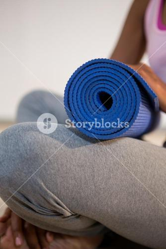 Woman holding exercise mat