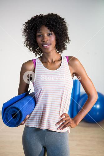 Portrait of smiling woman holding exercise mat