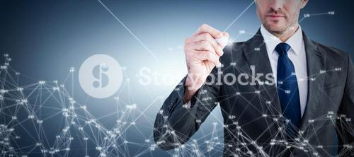Composite image of serious businessman writing with marker